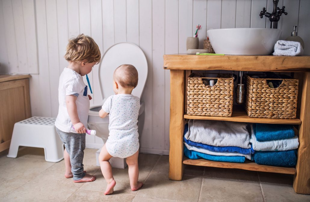 toddler and baby playing near toilet